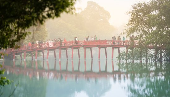 Bridge with people in fog. Hanoi, Vietnam.